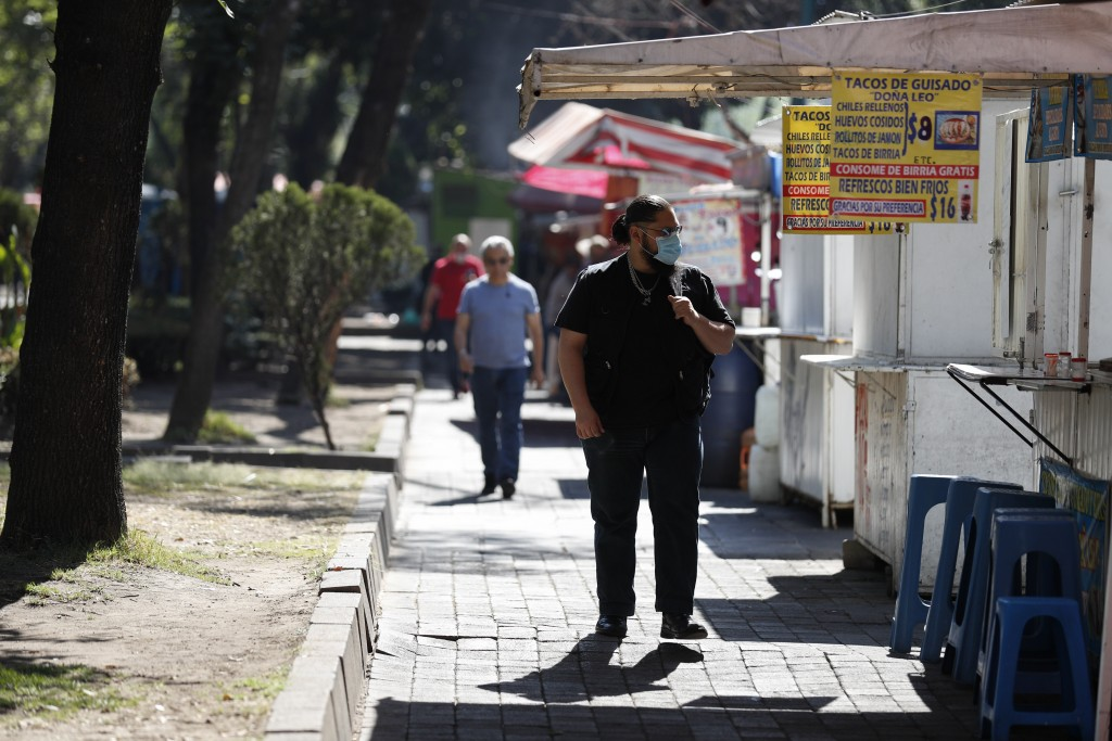 A man wearing a face mask walks past street stalls selling food, most of which were already open for business for the day, in Mexico City, Wednesday, ...
