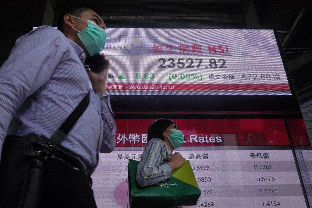 People wearing face masks walk past a bank electronic board showing the Hong Kong share index at Hong Kong Stock Exchange Thursday, March 26, 2020. As...