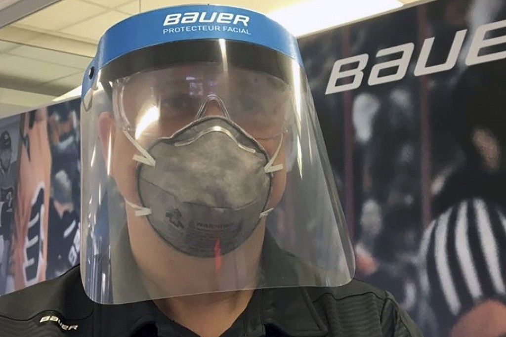 In this March 23, 2020, photo provided by Bauer Hockey Corp., an employee models a medical face shield the hockey equipment manufacturer has begun cre...