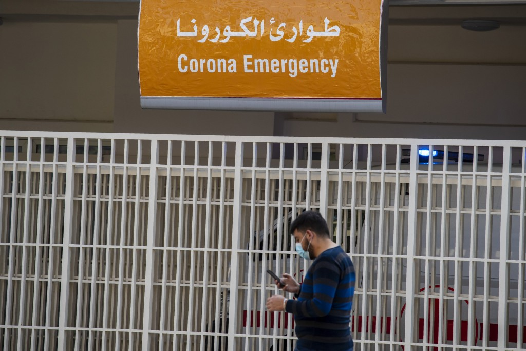 A man wears a mask as he checks his mobile phone while passing the emergency entrance of the government-run Rafik Hariri University Hospital where mos...