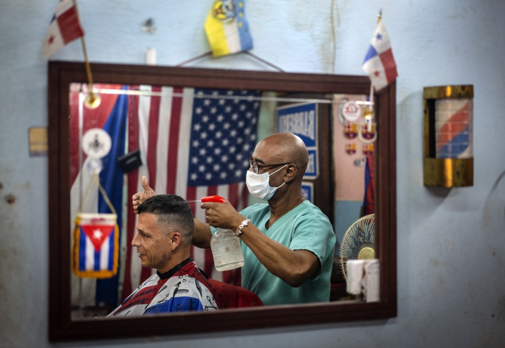 Barber Eugenio Lafargue, reflected in a mirror wearing a protective face mask against a precaution against the spread of the new coronavirus, styles a...