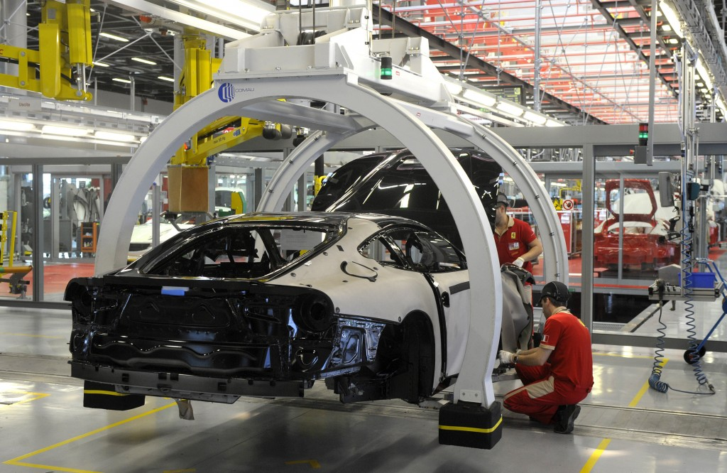 FILE - In this Wednesday, May 8, 2013 file photo, a technician works at the Ferrari department factory in Maranello, Italy. The eurozone's third-large...