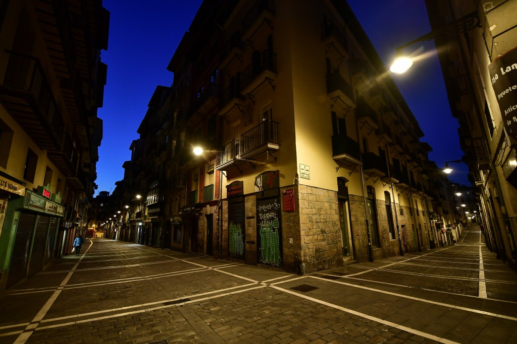 A pedestrian walks near to the corner between Estafeta, left, and Javier street of the old city, in Pamplona, northern Spain, Wednesday, March 25, 202...