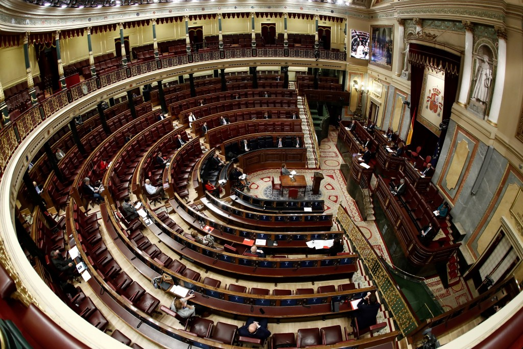 Spain's Prime Minister Pedro Sanchez, right, speaks in a nearly empty parliament while the majority of lawmakers follow the session online before a vo...