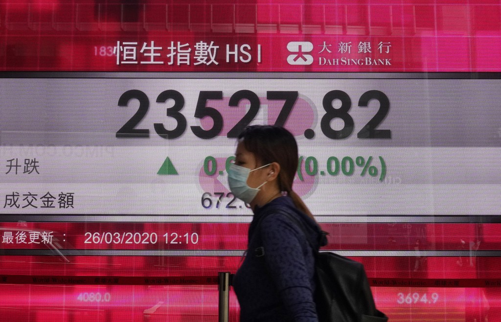 A woman wearing face mask walks past a bank electronic board showing the Hong Kong share index at Hong Kong Stock Exchange Thursday, March 26, 2020. A...