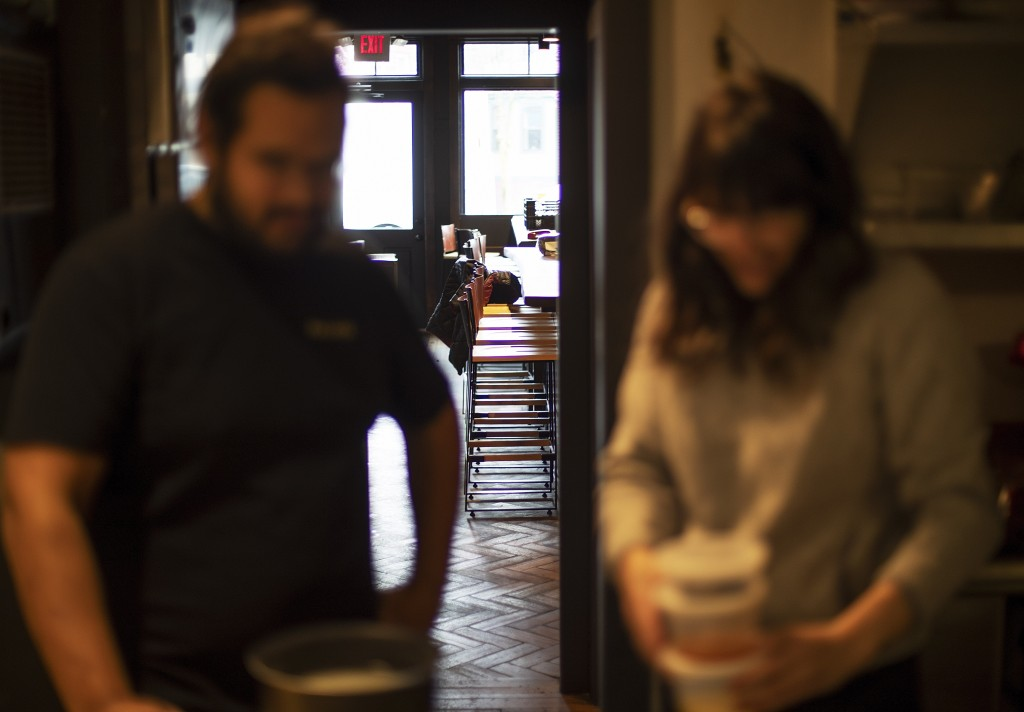 Empty stools stand in the background as James Mark, left, owner of the restaurant Big King, talks with Jennifer Wittlin as they prepare for dinner tak...