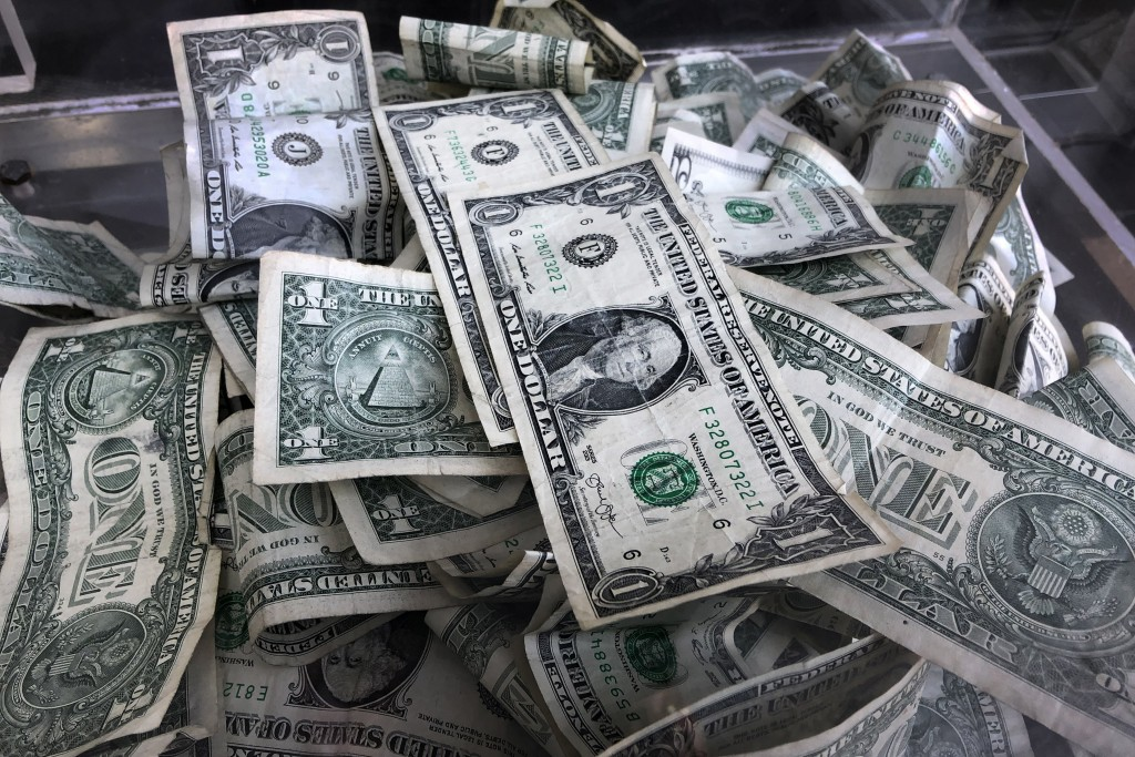 FILE - In this April 3, 2019, file photo a tip box is filled with U.S. currency in New York. Regularly checking in on your money is important. But it'...