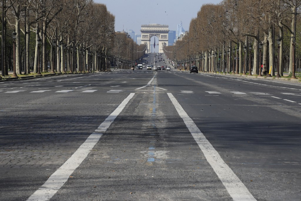 FILE - In this March 19 2020 file photo, the mostly empty Champs Elysees avenue is pictured in Paris, Thursday, March 19, 2020. The confinement measur...