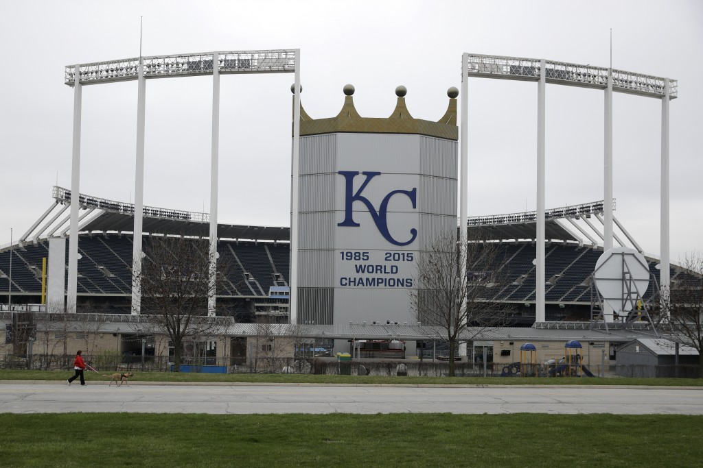 A woman and her dog walk past Kauffman Stadium, home of the Kansas City Royals baseball team, Wednesday, March 25, 2020, in Kansas City, Mo. The start...