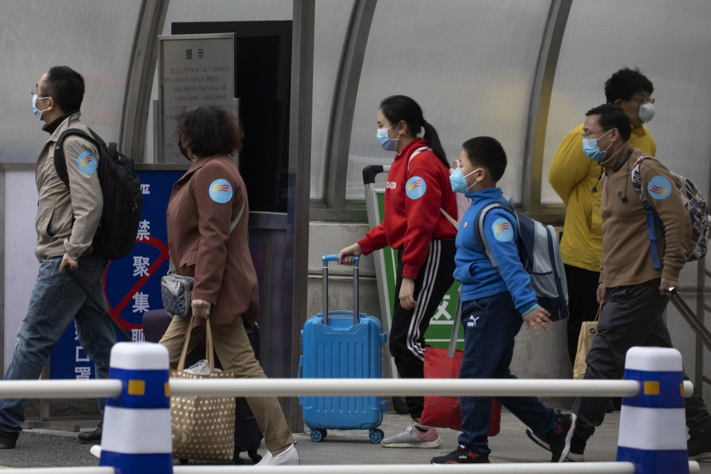 Returnees from the Hubei Province leave from the West Train Station to board buses in Beijing on Thursday, March 26, 2020. China is allowing people wh...