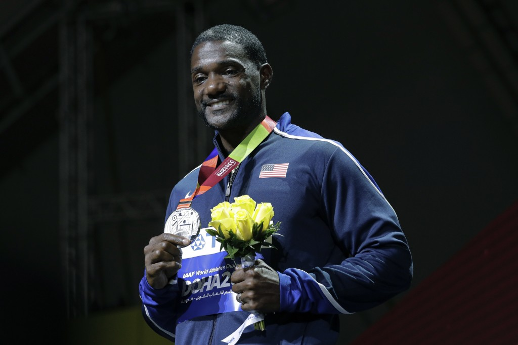 FILE - In this Sept. 29, 2019, file photo, silver medal winner Justin Gatlin, of the United States, smiles during the medal ceremony for the men's 100...