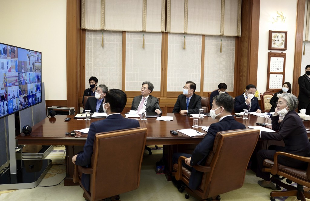 In this photo provided by South Korea Presidential Blue House via Yonhap News Agency, Presidential staffs watch a screen showing G-20 virtual summit t...