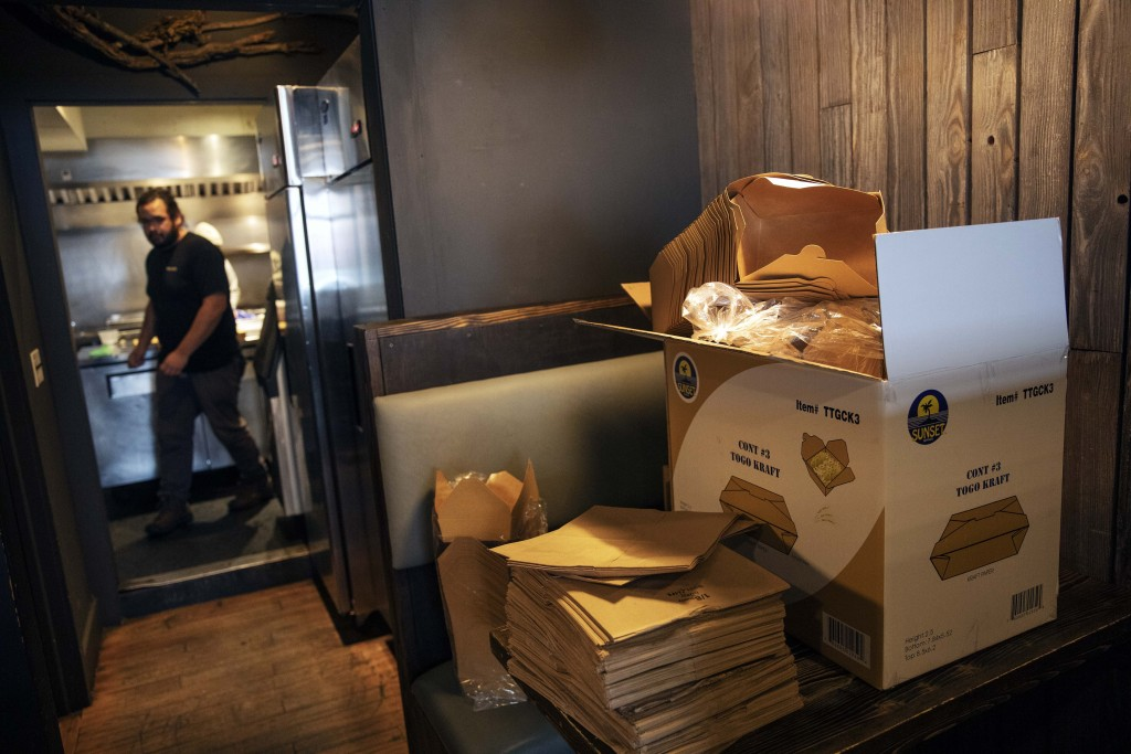 Take-out supplies sit on a table as James Mark, owner of the restaurant Big King, prepares for dinner take-out orders Wednesday, March 25, 2020, in Pr...