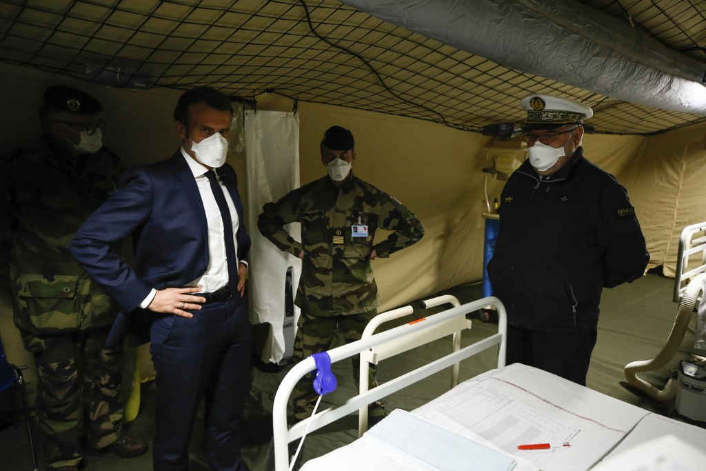 French President Emmanuel Macron, second left, wears a face mask as he visits the military field hospital in Mulhouse, eastern France, Wednesday, Marc...