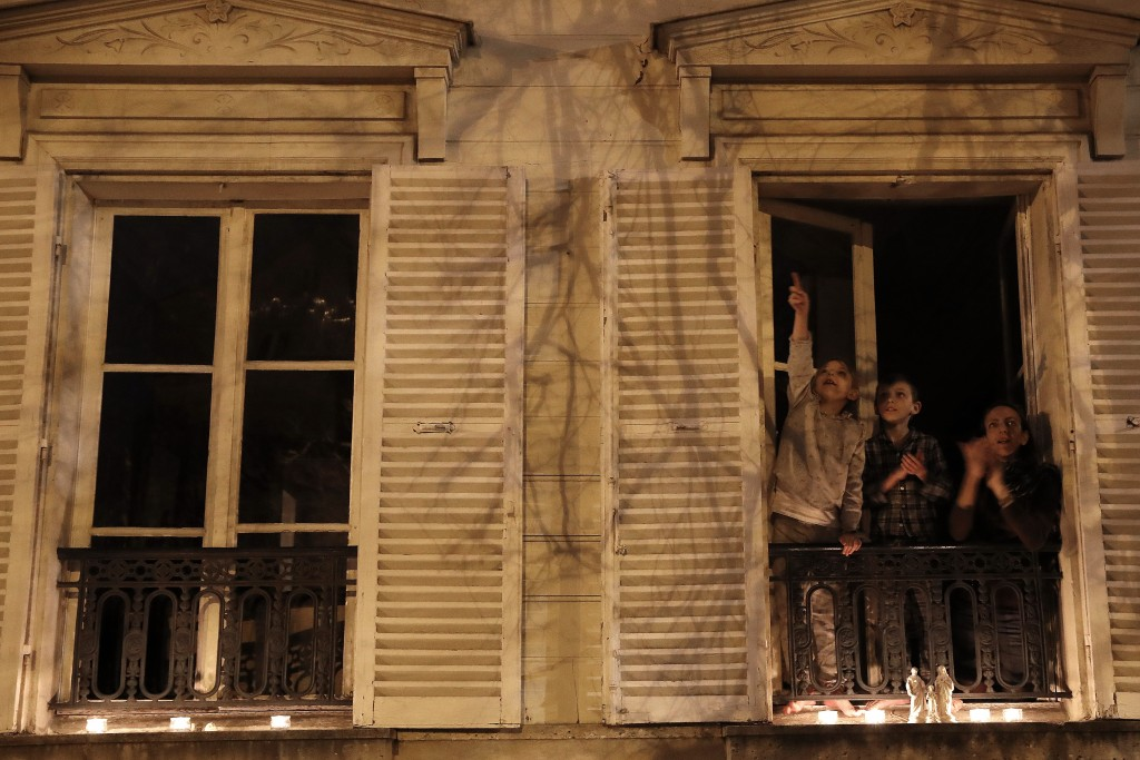 A woman and her children applaud after they set up candles on their balcony in Versailles, Wednesday, March 25, 2020. France's bishops called for Cath...