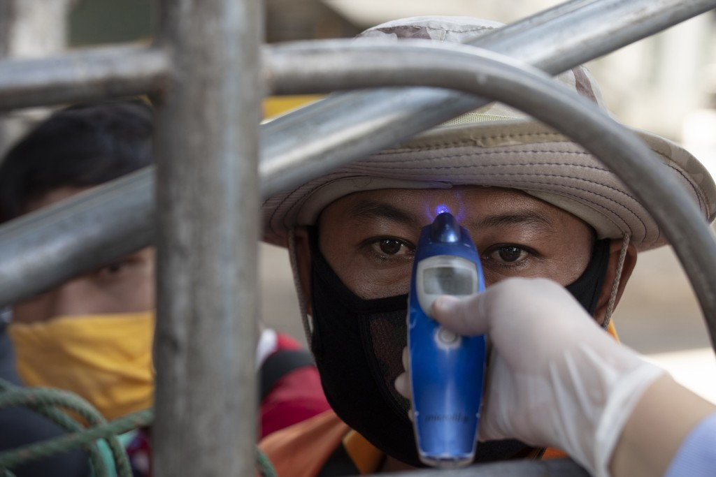 A health officer checks the temperature of a passenger in truck at a health check point in Bangkok, Thailand, Thursday, March 26, 2020. The country is...