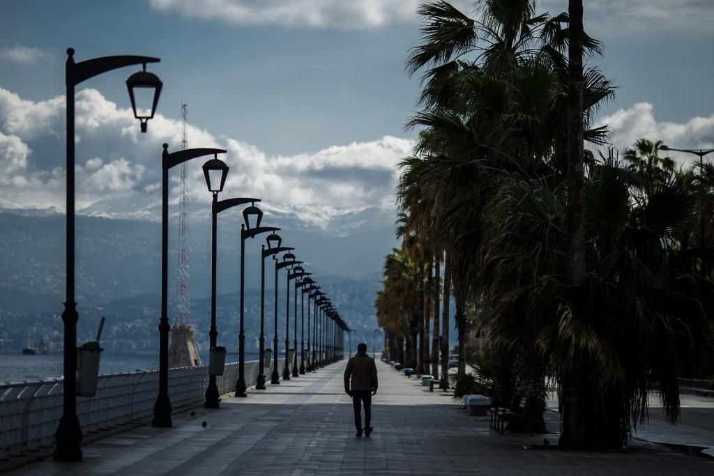 A man walks at Beirut's seaside corniche, or waterfront promenade, along the Mediterranean Sea, which is almost empty of residents and tourists in Bei...