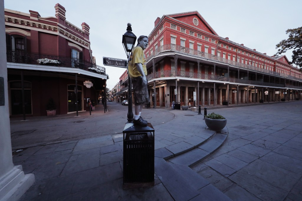 FILE - In this Sunday, March 22, 2020, file photo, street performer Eddie Webb looks around the nearly deserted French Quarter looking to make money i...