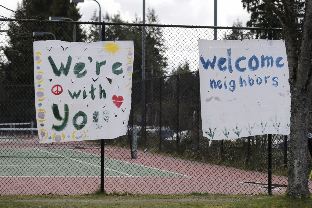 In this photo taken Tuesday, March 24, 2020, handmade signs posted to a tennis court fence are set to greet future patients at a temporary field hospi...