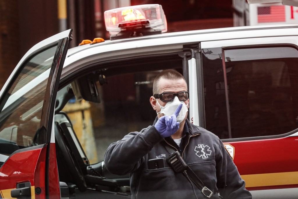 An FDNY medical worker wears personal protective equipment outside a COVID-19 testing site at Elmhurst Hospital Center, Wednesday, March 25, 2020, in ...