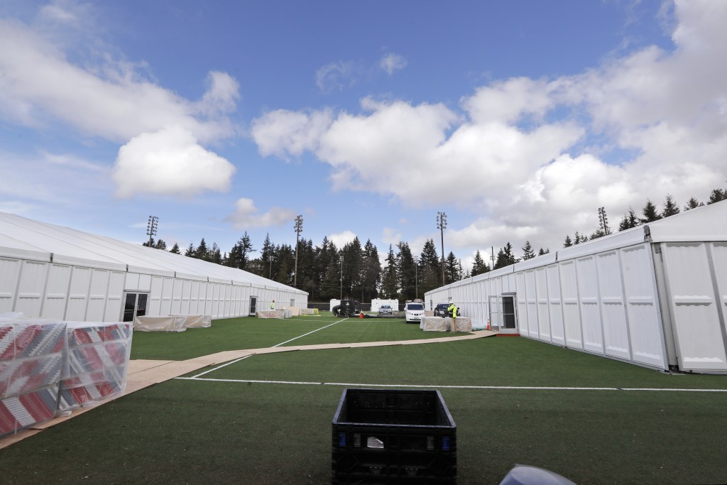 In this photo taken Tuesday, March 24, 2020, two massive temporary buildings meant for use as a field hospital for coronavirus patients stand together...