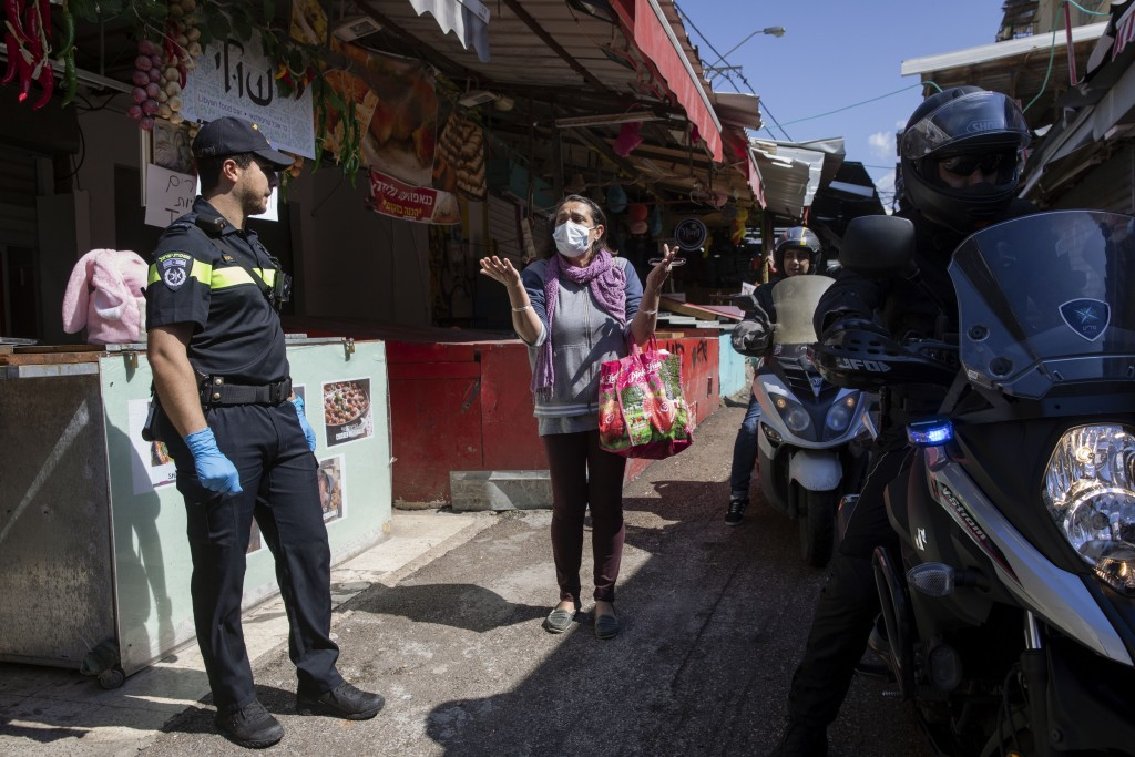 A woman argues with a police officer as police shut down a food market in order to reduce the spread of the coronavirus, in Tel Aviv, Israel, Sunday, ...