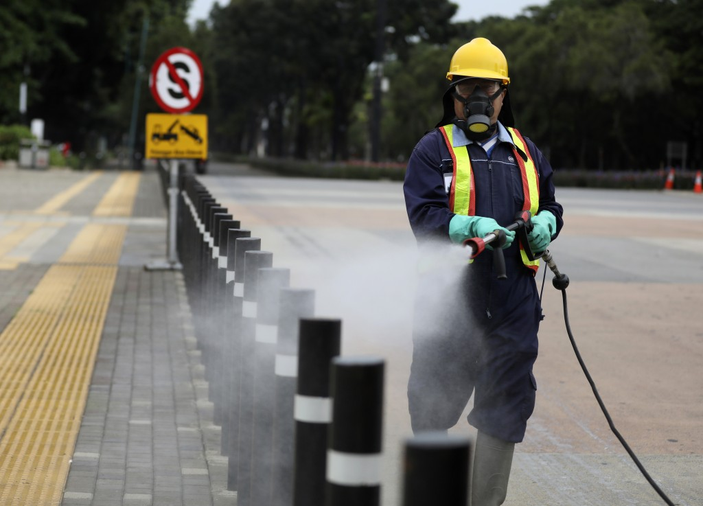 A worker sprays disinfectant at the pedestrian walkway at Senayan Sports Complex amid coronavirus outbreak, in Jakarta, Indonesia, Thursday, March 26,...