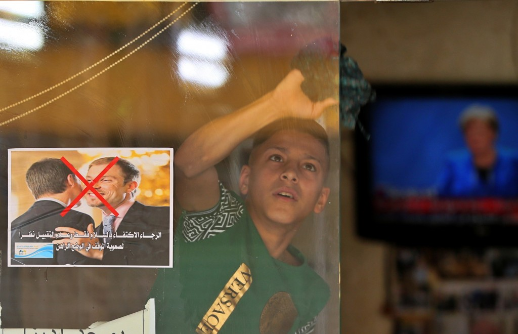 """A young worker cleans the window of a barbershop that posts a warning sign referring to the coronavirus, with Arabic that reads, """"Please greet only an..."""