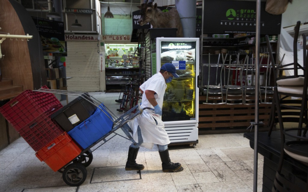 An employee wearing a protective face mask and disposable gloves, hauls crates with the aid of a trolley through the popular and normally crowded San ...