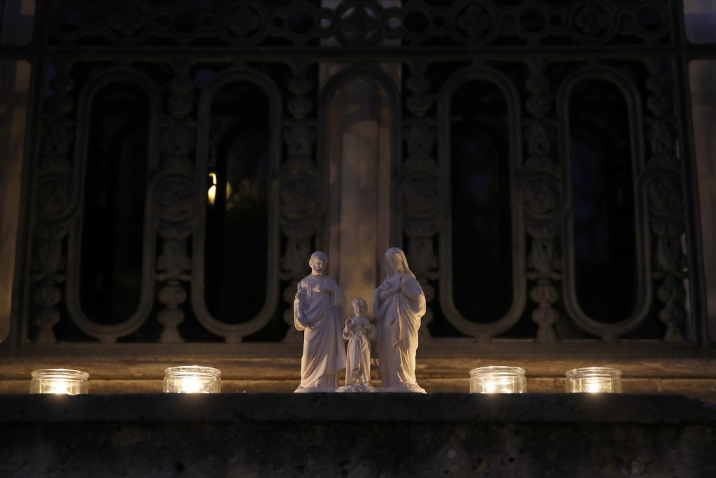 Candles are set up on a balcony in Versailles, Wednesday, March 25, 2020. France's bishops called for Catholics and non-Catholics alike to take part i...