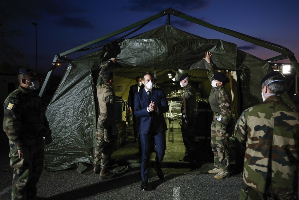 French President Emmanuel Macron wears a face mask during his visit at the military field hospital in Mulhouse, eastern France, Wednesday, March 25, 2...