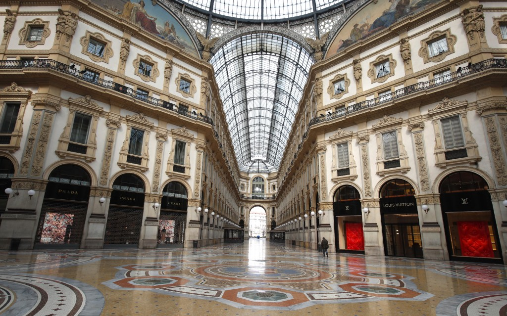 FILE - In this Sunday, March 22, 2020 filer, a man walks in an empty Vittorio Emanuele II gallery shopping arcade, in downtown Milan, Italy. The euroz...