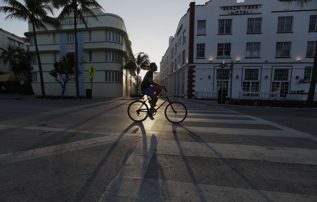 A cyclist rides past Art Deco hotels on normally bustling streets as the sun sets, Wednesday, March 25, 2020, in Miami Beach, Florida's famed South Be...