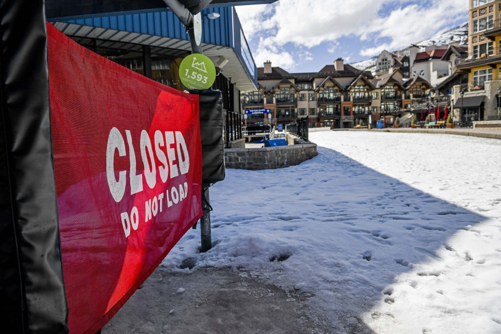 In this Tuesday, March 24, 2020, photo a sign hangs on a closed ski lift in Vail, Colo., after Vail Ski Resort closed for the season amid the COVID-19...