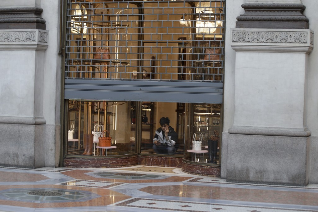 FILE - In this Wednesday, March 11, 2020 filer, a cleaner sits in a shut down shop at the Vittorio Emanuele shopping arcade in Milan, Italy. The euroz...