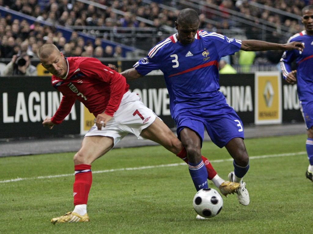 FILE - In this Wednesday, March 26, 2008 file photo England's David Beckham, left, challenges for the ball with France's Eric Abidal during their frie...