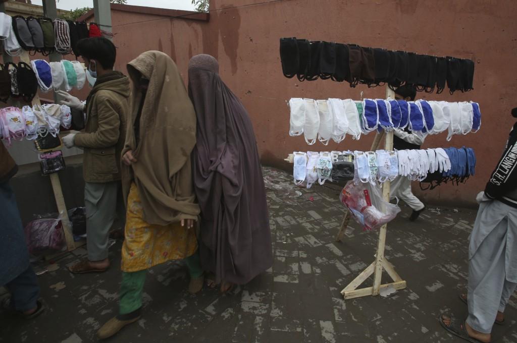 Pakistani women walk past vendors selling face masks to prevent the spread of the coronavirus, in Peshawar, Pakistan, Tuesday, March 24, 2020. Pakista...