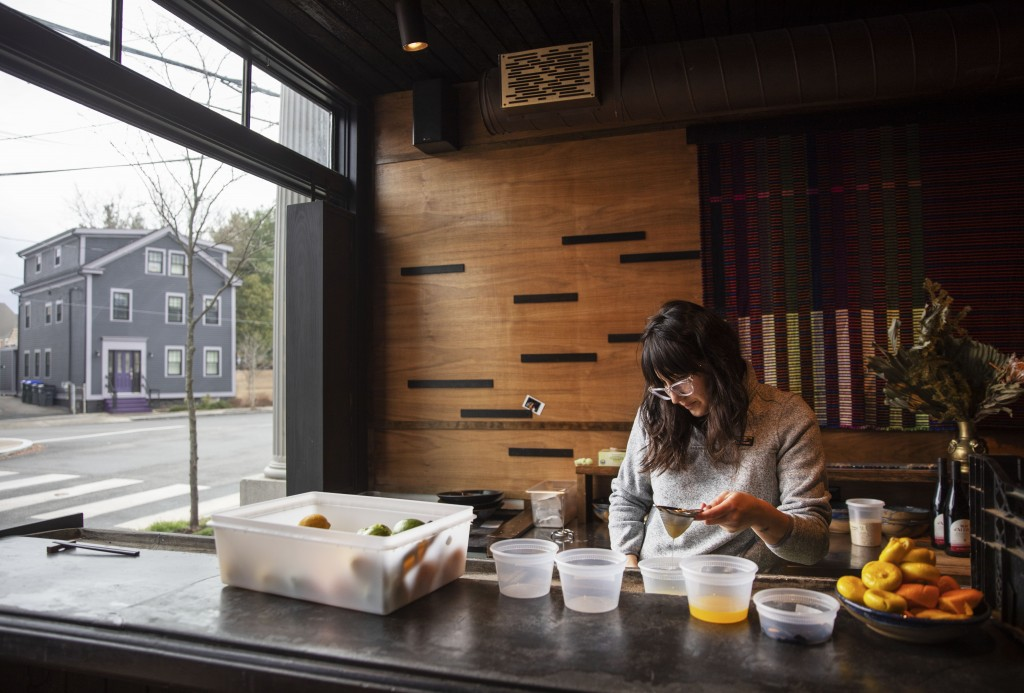 Jennifer Wittlin prepares for dinner take-out orders at Big King on terriWednesday, March 25, 2020, in Providence, R.I. Owner James Mark said pushing ...