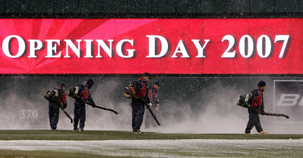 FILE - In this April 6, 2007, file photo, members of the Jacobs Field grounds crew use leaf blowers to clear snow from the field during a delay in the...
