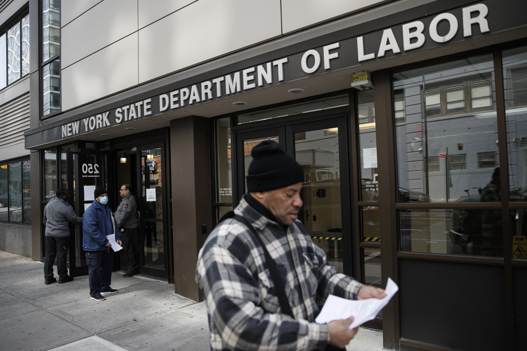 FILE - In this March 18, 2020 file photo, visitors to the Department of Labor are turned away at the door by personnel due to closures over coronaviru...