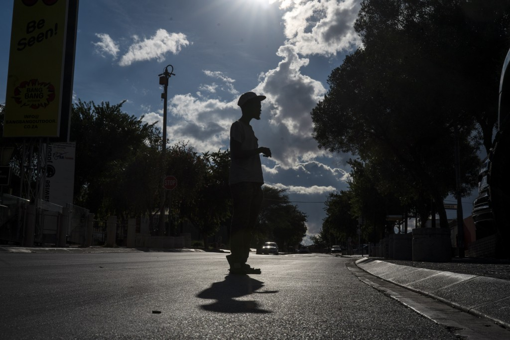 A parking guard stands in the deserted Vilakazi street in the township of Soweto, near Johannesburg, South Africa, Thursday March 26, 2020, just hours...