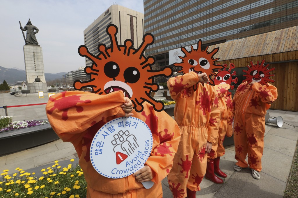 Environmental activists wearing masks symbolizing a virus perform during a new coronavirus prevention campaign in Seoul, South Korea, Thursday, March ...