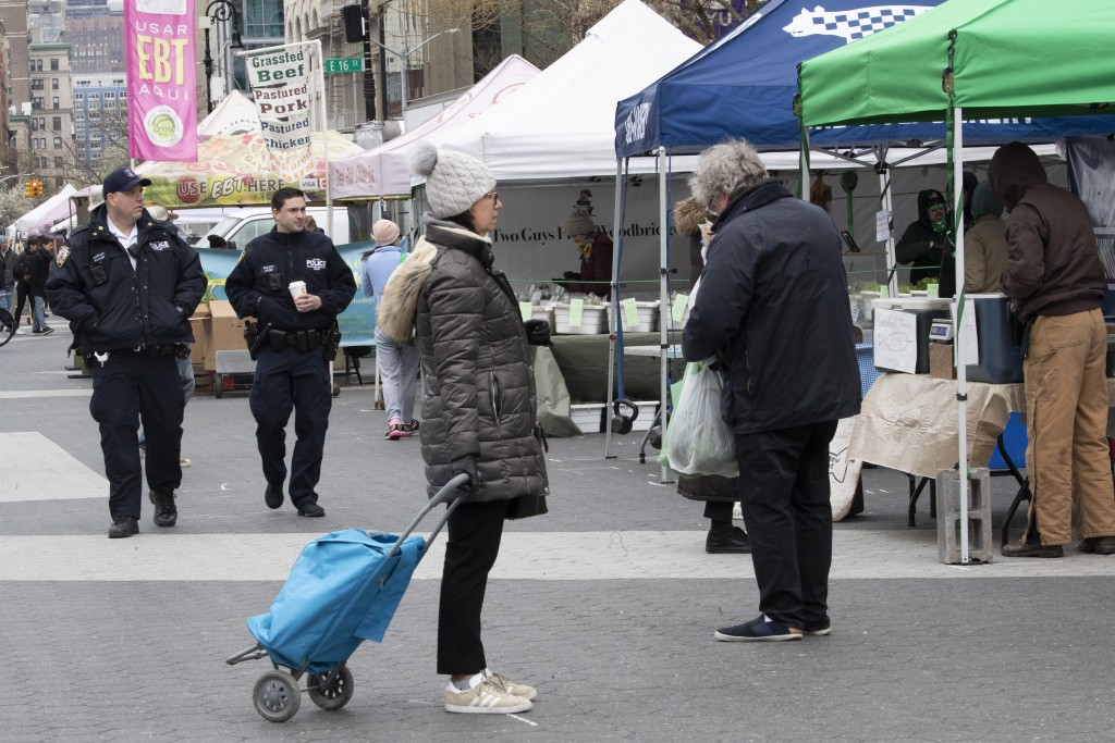 A shopper stands on a social distancing marking as police officers patrol the farmers market in Union Square, Wednesday, March 25, 2020, in New York. ...