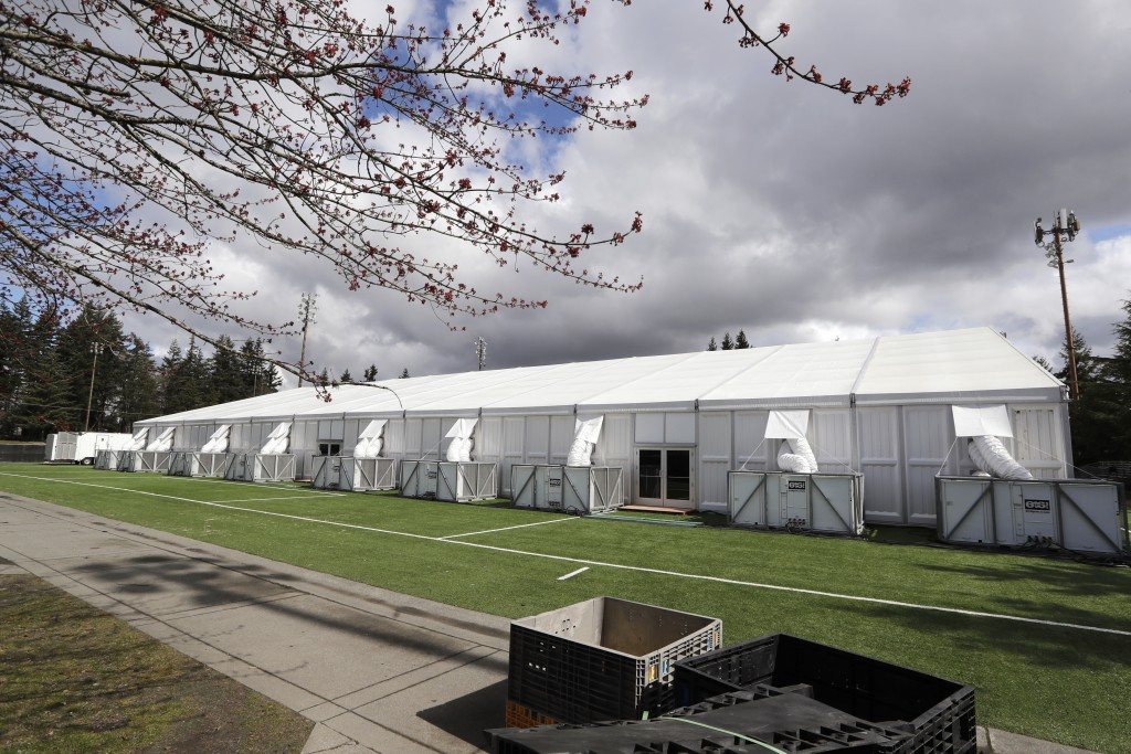 In this photo taken Tuesday, March 24, 2020, one of a pair of massive temporary buildings meant for use as a field hospital for coronavirus patients s...