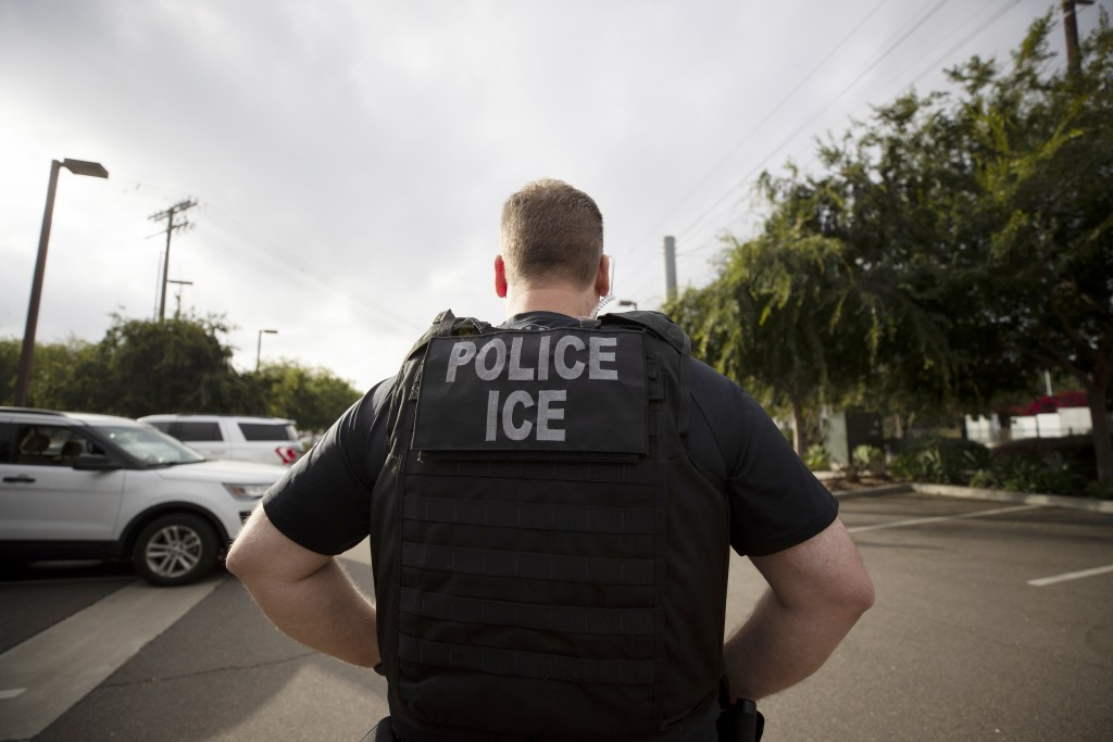 FILE - In this July 8, 2019, file photo, a U.S. Immigration and Customs Enforcement (ICE) officer looks on during an operation in Escondido, Calif.  P...