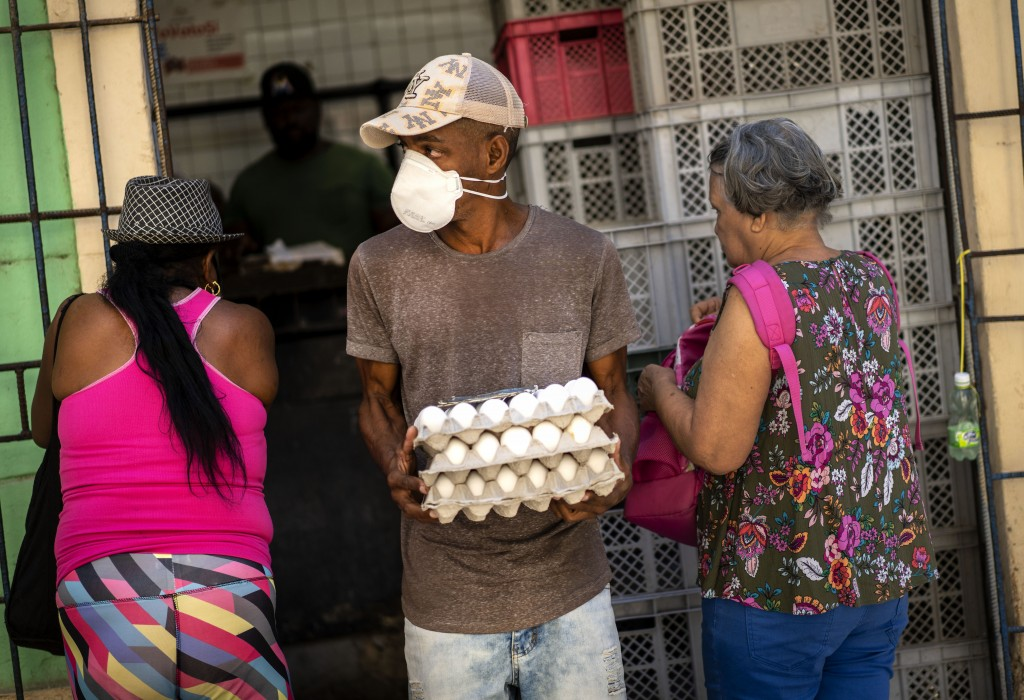 A man wearing a protective face mask against a precaution against the spread of the new coronavirus, exits a government store with his ration of eggs,...