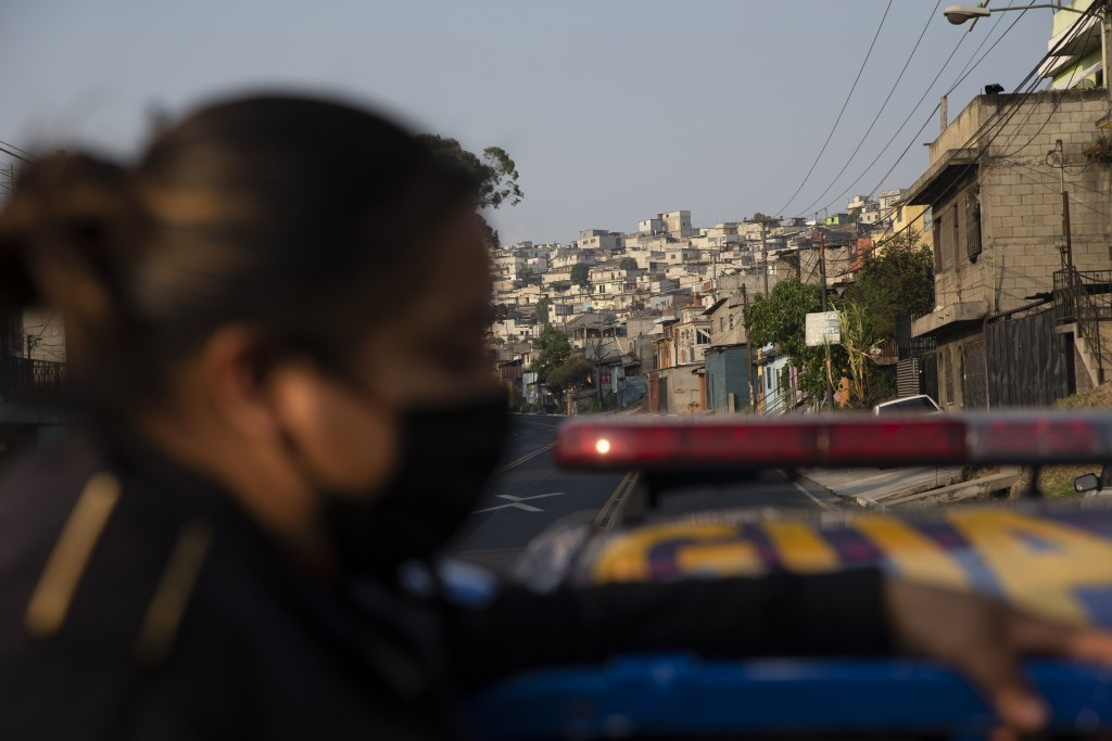 A police officer patrols during the fourth day of a curfew across the country to help prevent the spread of the new coronavirus in Villa Nueva, Guatem...