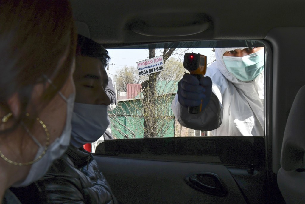 In this Wednesday, March 25, 2020, photo, a medical worker checks temperatures of a car passengers at a checkpoint near Bishkek, Kyrgyzstan. For most ...