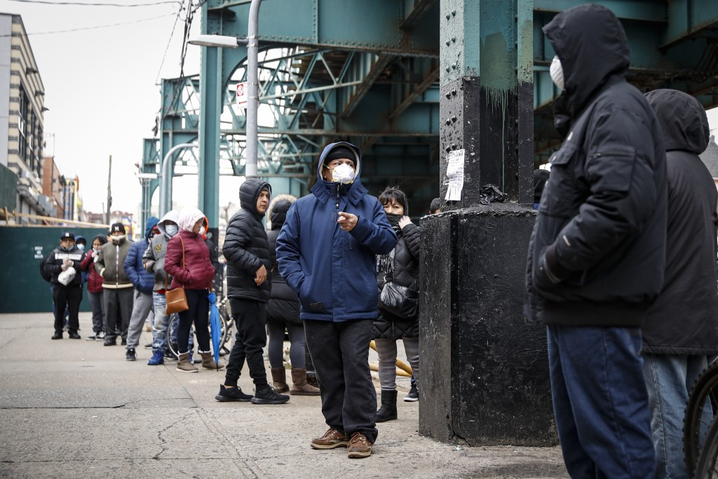 Patients wait in line outside an urgent care pharmacy while wearing personal protective equipment, Wednesday, March 25, 2020, in the Queens borough of...