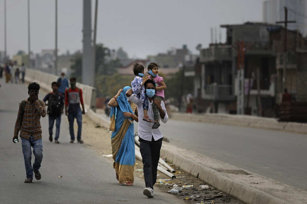 An Indian man carries his children on his shoulders as he along with his family walk along an expressway hoping to reach their home, hundreds of miles...